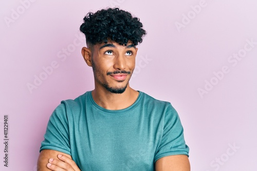 Vászonkép Young arab handsome man wearing casual clothes smiling looking to the side and staring away thinking