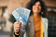 Young Hispanic Businesswoman Smiling Happy Holding Chilean Pesos Banknotes At The City.