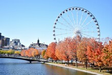 Ferris Wheel By River Against Sky During Autumn