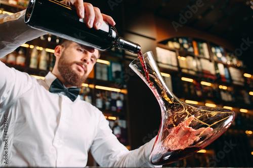 Young handsome man sommelier tasting red wine in cellar. Fototapeta