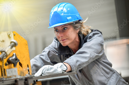 Leinwand Poster Concentrate woman worker using a punching machine