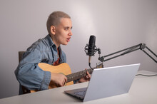 Young Hipster Woman Is Recording A Song At Home Recording Studio. A Girl Plays An Acoustic Guitar Sings Into A Microphone Records Video On A Laptop