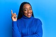 canvas print picture - Young african american woman wearing casual winter sweater with a big smile on face, pointing with hand and finger to the side looking at the camera.