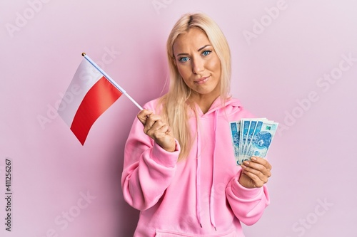 Wallpaper Mural Young blonde woman holding poland flag and zloty banknotes relaxed with serious expression on face