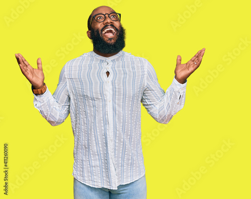 Fototapeta Young african american man wearing business shirt and glasses celebrating mad and crazy for success with arms raised and closed eyes screaming excited. winner concept obraz