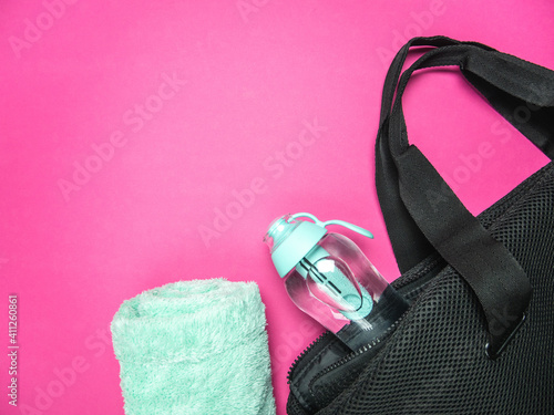 Filter water bottle in a training bag and towel. Fitness flat lay composition with copy space on pink background.