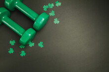 Green Dumbbells And Clover For St. Patrick's Day. Composition On Black Backdrop With Copyspace.