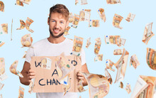 Young Caucasian Man Holding We Need A Change Banner Looking Positive And Happy Standing And Smiling With A Confident Smile Showing Teeth