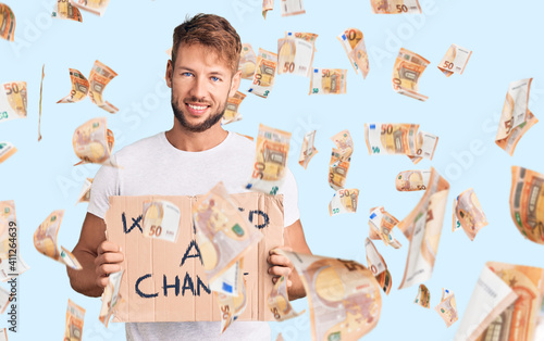 Fototapeta Young caucasian man holding we need a change banner looking positive and happy s