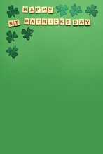 Wooden Letters Making The Phrase Happy Saint Patricks Day And Green Clovers On A Green Background, Top View Place For Text