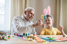 Happy Elderly Man Granfather Preparing For Easter With Grandson. Portrait Of Smiling Boy With Bunny Ears Painted  Colored Eggs For Easter