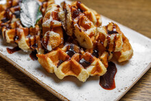Freshly Baked Shortbread Waffles, Drizzled With Chocolate, Decorated With Basil Leaves, Served On A Rectangular Plate On A Wooden Background. Dessert At The Restaurant.