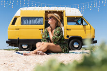 Young Blonde Woman Travelling By Vintage Campervan At The Seaside. Relaxing On The Beach.