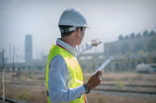Portrait asian manager engineer in hardhat at work on outside industrial,using digital tablet control work and survey building construction factory site,concept action business working and industry Fototapete