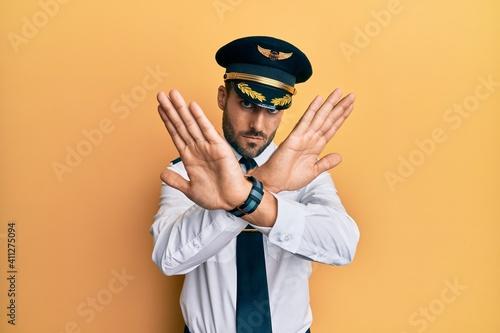 Fotografia, Obraz Handsome hispanic man wearing airplane pilot uniform rejection expression crossi