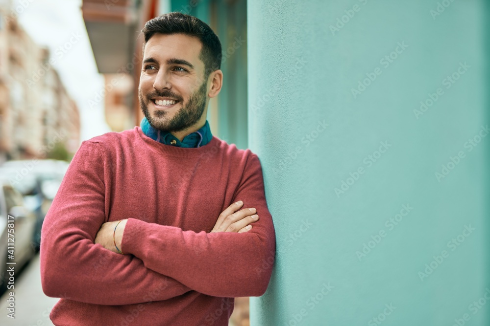 Fototapeta Young hispanic man smiling happy standing at the city.