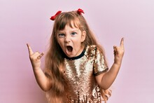 Little Caucasian Girl Kid Wearing Festive Sequins Dress Shouting With Crazy Expression Doing Rock Symbol With Hands Up. Music Star. Heavy Concept.