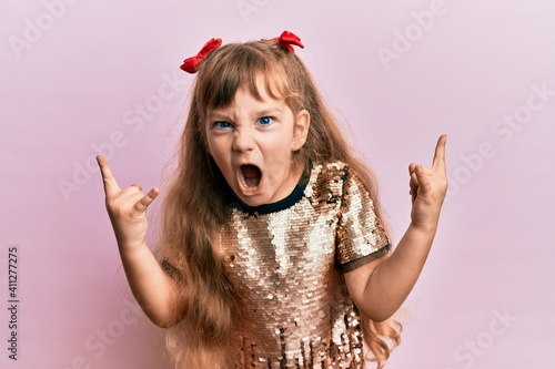 Obraz Little caucasian girl kid wearing festive sequins dress shouting with crazy expression doing rock symbol with hands up. music star. heavy concept. - fototapety do salonu