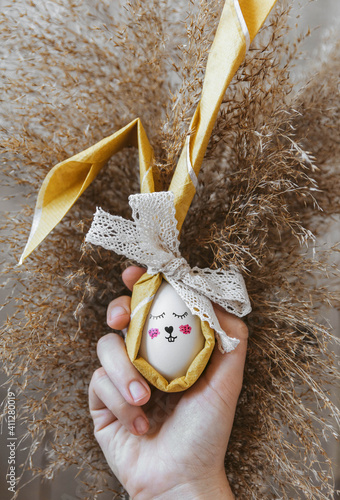 Obraz na plátne Hand Holding Easter Egg Crafted Into A Bunny.