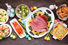 Traditional Easter Ham Dinner. Top Down View Table Scene On A Dark Wood Background. Ham, Scalloped Potatoes, Vegetables, Eggs, Hot Cross Buns And Carrot Cake.