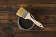 Brush on an open jar with a tinting composition on a wooden background.