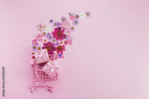 Foto Flowers fly out of the pink shopping cart on a pink background