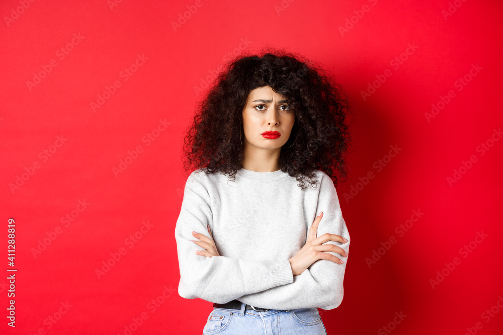 Fototapeta Sad and worried caucasian woman frowning, cross arms on chest and looking concerned, feeling bad, standing on red background