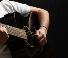 Young Man Playing Guitar, Close Up View, Dark Background.