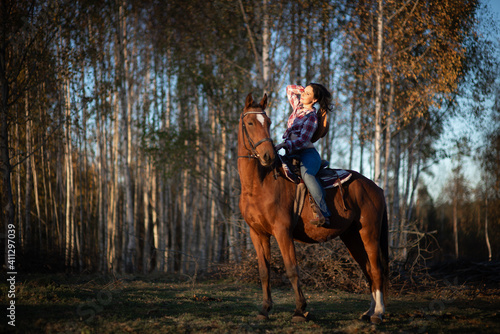 Slika na platnu A Woman Wearing A Cowboy Hat Rides A Horse In A Countryside Farm Yard,natural So