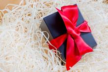 Pequeña Caja Negra Con Lazo Rojo Y Fondo Claro
