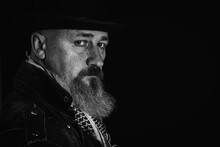 Black And White Photo, Portrait Of A Serious, Bearded Man In A Black Hat On A Dark Background. Low Key. Emotional Portrait