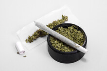 Grinder Full Of Dry Herb And Joint With Medical Marijuana With Paper Filter And Piece Of Rolling Paper On White Background