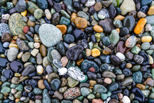 Colorful Smooth Rocks On The Beach Covered In Water.