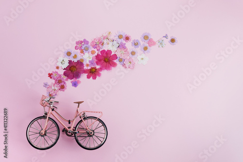 Obraz Flowers fly out from pink bicycle bascet on pink background. Romanitic concept for Valentine day, women or mother day. - fototapety do salonu