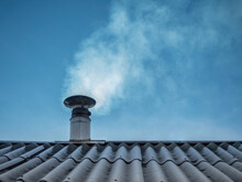 Chimney Emits Smoke Against The Blue Sky