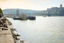 Boats Line The Banks Of The Danube River Near The Shoes On The Danube Memorial With The Chain Bridge And Royal Palace Behind, In Budapest, Hungary