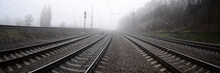Diminishing Perspective Of Railroad Tracks Against Sky During Foggy Weather