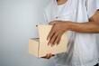 Leinwandbild Motiv Midsection Of Man Holding Cardboard Box While Standing Against Wall
