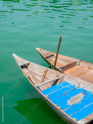Obraz na płótnie Pair of traditional wooden Vietnamese sampan rowboats on calm water