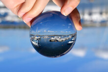 Upside Down Image Of Hand Holding Crystal Ball At Harbor