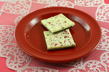 White Chocolate Peppermint Bark On Top Of Dark Chocolate Candy On Red Plate On Heart Lace Tablecloth Runner