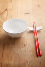 High Angle View Of Empty Bowl With Chopsticks On Wooden Table