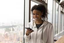 Smiling Young African American Lady Spend Free Time At Home In Office Use Cellphone App. Content Millennial Black Female Stand By Large Picture Window With Splendid Urban View Messaging By Cell Online
