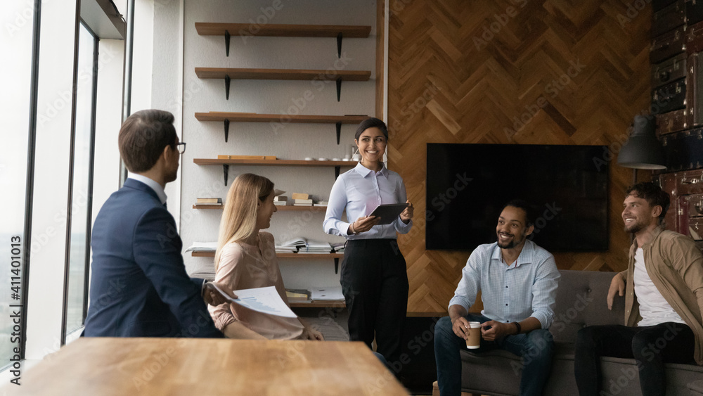 Fototapeta Successful multiethnic business team sharing experience discuss project sales strategy at informal briefing. Young indian female hold tablet pc speak on staff meeting training in friendly atmosphere