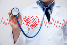 Midsection Of Doctor Holding Stethoscope With Pulse Trace