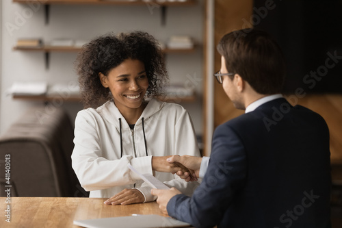 Thank you for good advice. Appreciative young african lady client shake hand of trusted male manager acknowledging his help. Glad black woman handshaking with agent after signing life insurance policy