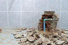 Plumbing Problems. A Wall Of A Bathroom Is Opened To Find A Leak From A Pipe Leaving Rubble On The Floor.