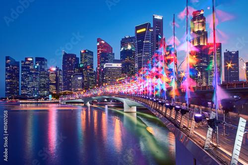 Fototapeta Illuminated Modern Buildings By River Against Sky At Night