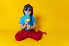Boy Child Eats Ice Cream Made Of Colored Paper On A Yellow Background