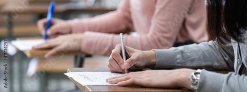 Close up of a woman student's hand writing on notepad placed on wooden desktop